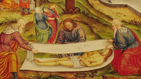 Тело Иисуса Христа укрывают плащаницей
