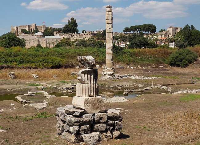 Одинокая колонна на фоне современного города